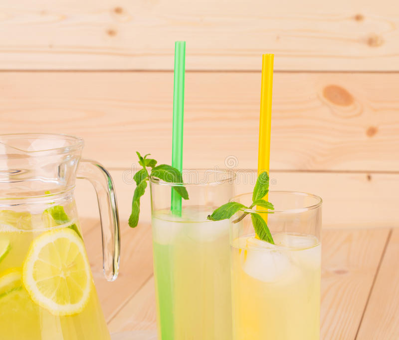 Pitcher and glass full of tasty lemonade. Wooden background royalty free stock photos