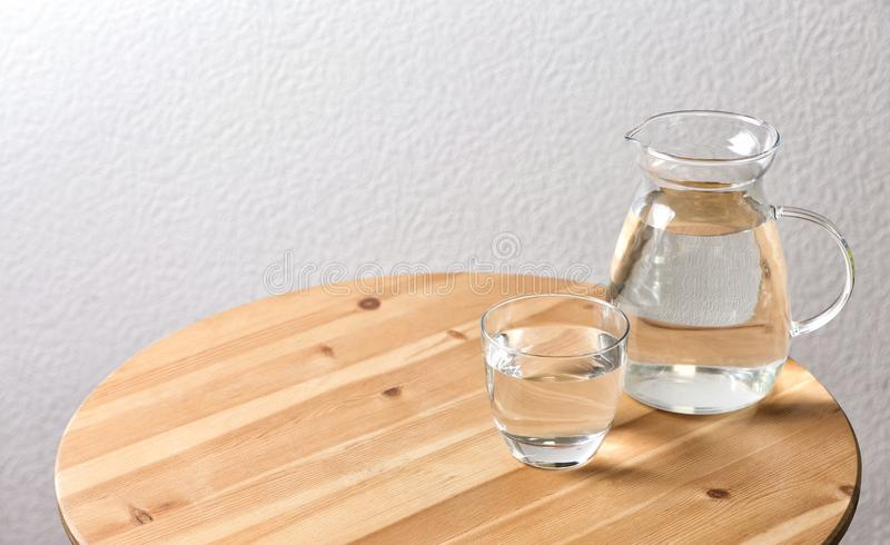 Pitcher and glass with water on table near white wall stock image