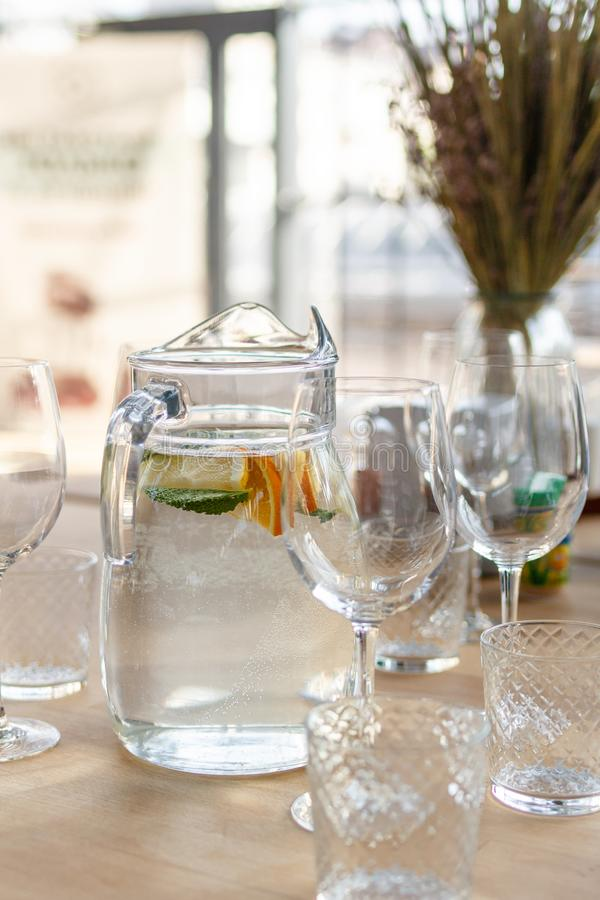 Pitcher of homemade lemonade drink of soda water, lemon, orange and fresh mint leaves on wooden table with a lot of stock photography