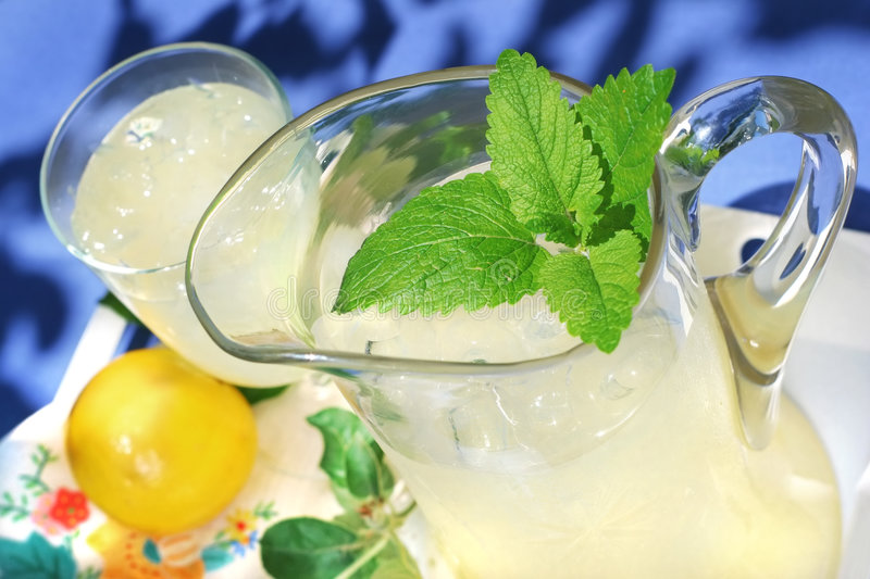 Pitcher of Lemonade with a sprig of mint royalty free stock images