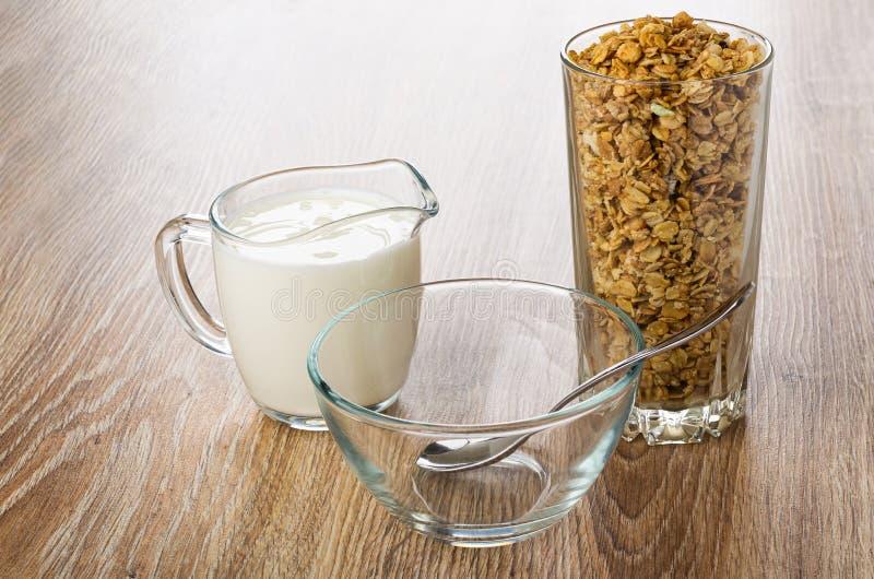 Pitcher mit Jogurt, hohes Glas mit Frucht muesli, Teelöffel in der Schüssel auf Holztisch stockfotografie