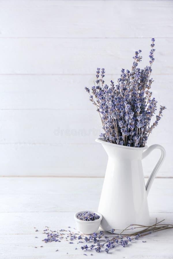 Pitcher mit schönen Lavendelblumen auf weißem Holztisch lizenzfreie stockfotografie
