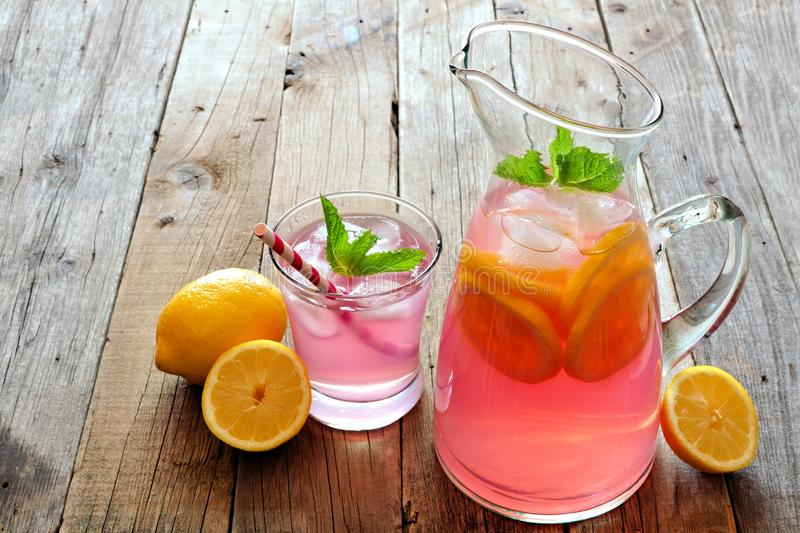 Pitcher of pink lemonade with filled glass on rustic wood royalty free stock photo