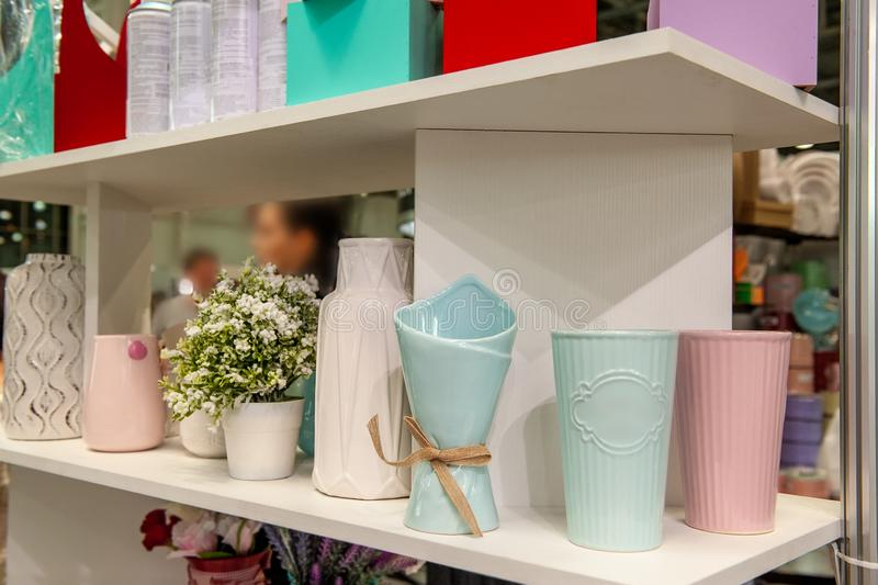 A pitcher, a set of clean dishes and vases for flowers on white shelves stock photos