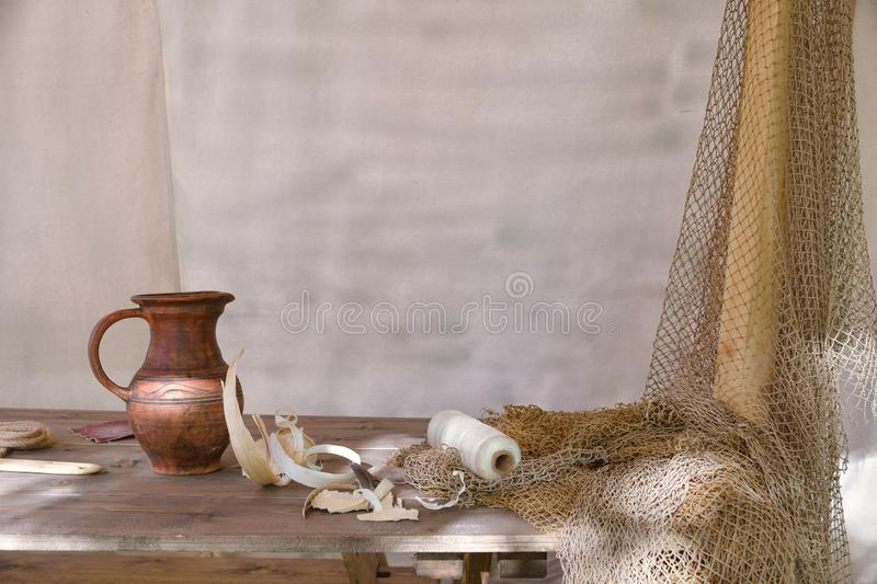 Pitcher on a table with a fishing net stock photos