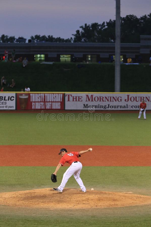 Pitcher throws from the mound. Submarine-style Pitcher throws from the mound at a pro baseball game stock image
