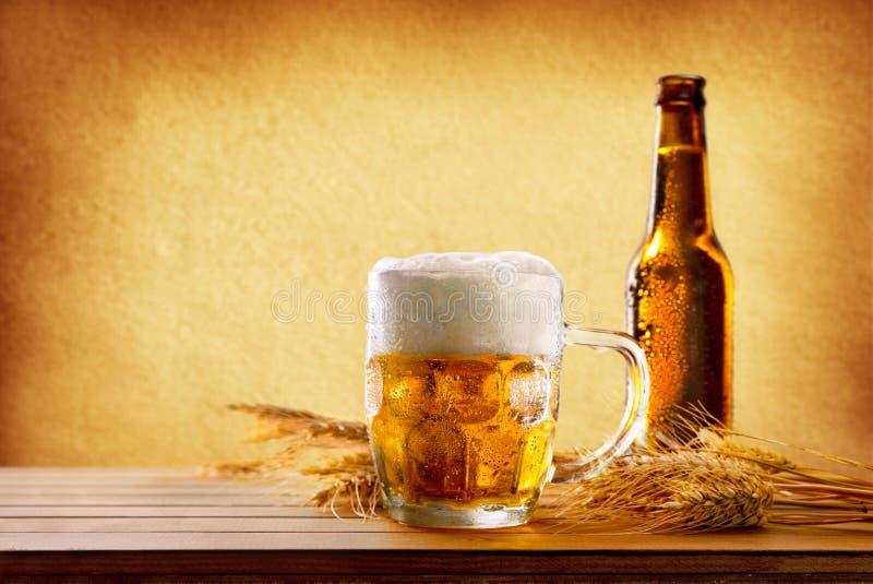 Pitcher voll Bier mit Schaum mit den Gerstenohren lizenzfreie stockfotos