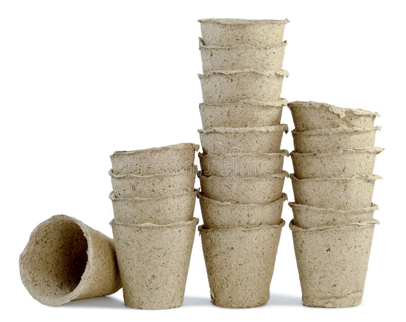 Pitchers peat a row. A lot of cups of peat for seedlings of plants inserted into one another and are installed in a row isolated on white background royalty free stock image
