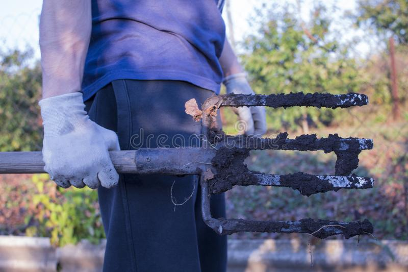 A pitchfork in a man`s hand. Close-up. On a natural background. There is a place for text. royalty free stock image