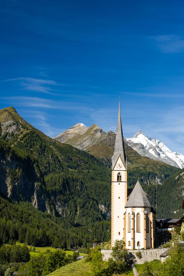 Pitcuresqe Church in Austria Village. High Alps Mountains in Background royalty free stock image