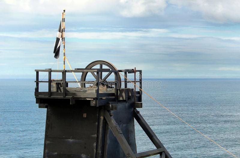 The pithead of a Cornish tin mine showing the main lifting pulley, with a Cornish nationalist Kernow flag stock image