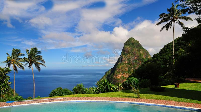 Piton between palm trees. Pool, Blue ocean, palm trees and clear blue sky, with a mountain know as Piton erected from the sea, summons the ambiance found in the stock images