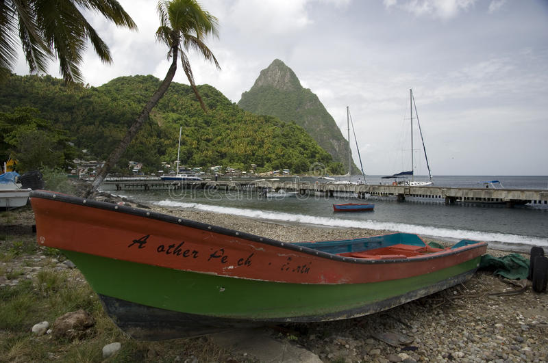 The pitons and boat St Lucia. The Pitons and boats St Lucia. Saint Lucia is an Eastern Caribbean island nation with a pair of dramatically tapered mountains, the royalty free stock images
