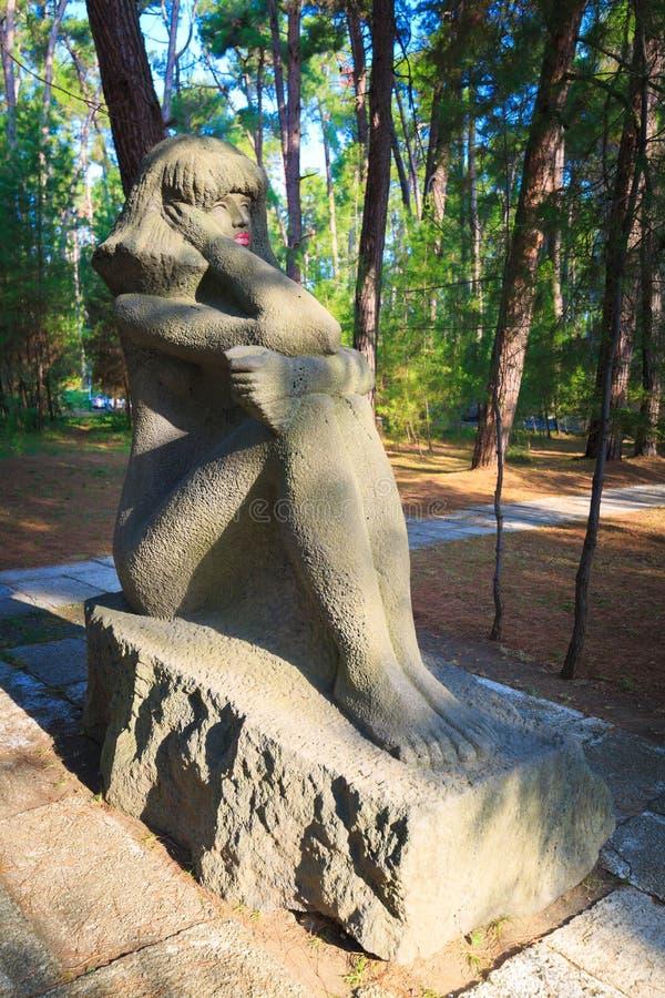 PITSUNDA ABCHAZIEN, SEPTEMBER 16, 2017: Stena skulptur av en sammanträdeflicka i Pitsunda royaltyfria foton