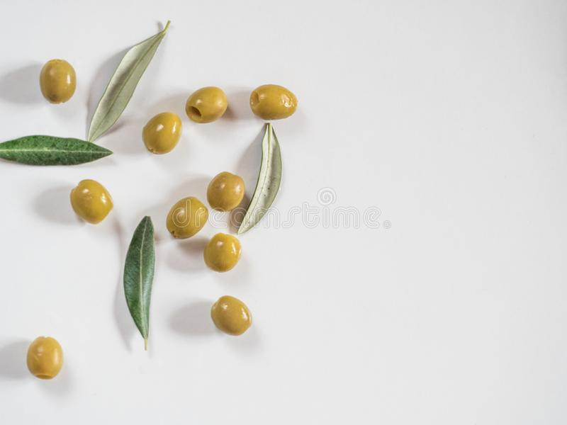 Pitted olives and leaves on white with copy space stock photo