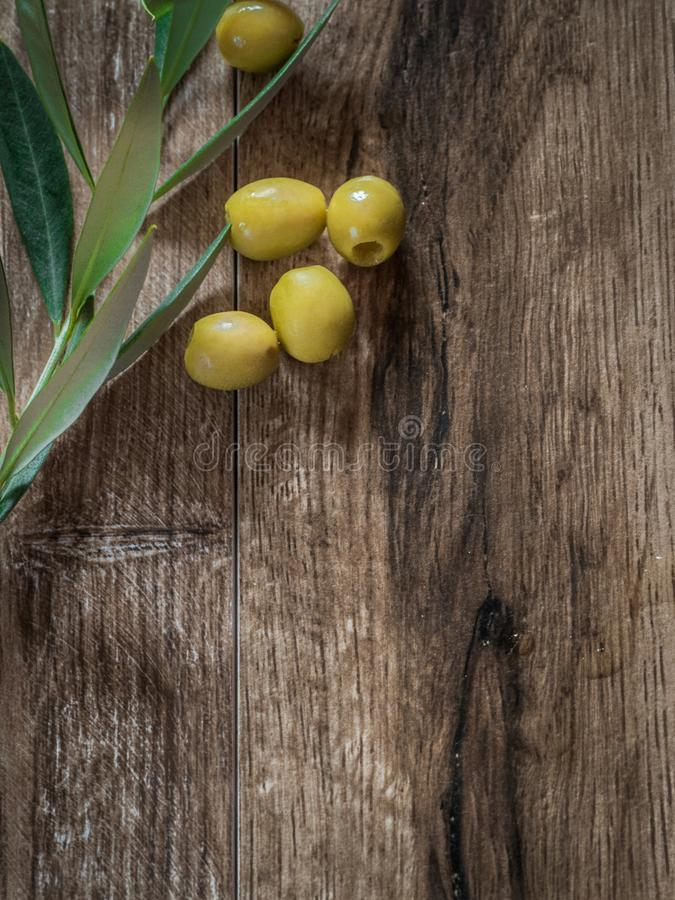 Pitted olives with leaves on wood with copy space stock photography