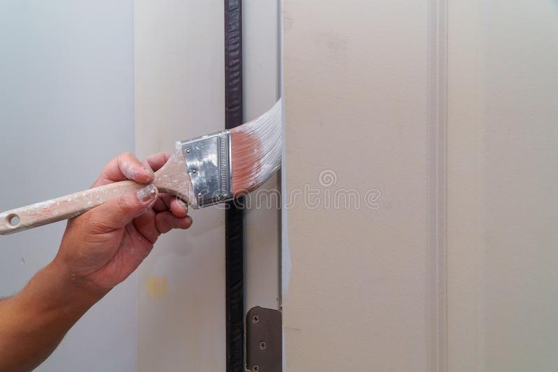 Pittore che dipinge il bianco della porta in nuova casa fotografie stock libere da diritti
