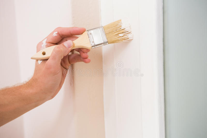 Pittore che dipinge la porta bianca immagine stock