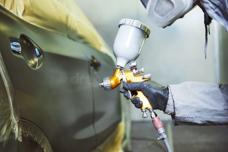 Pittore del riparatore nel cofano dell'automobile dell'automobile della pittura della camera fotografia stock