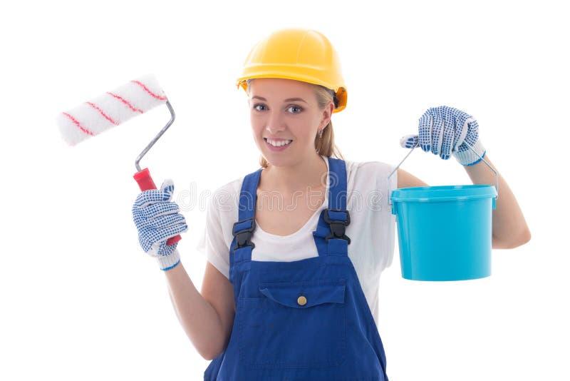Pittore della giovane donna in uniforme blu del costruttore con il pennello e fotografie stock libere da diritti