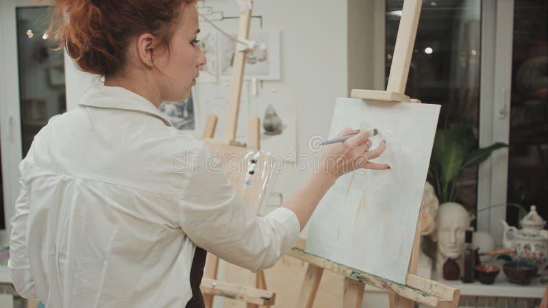 Pittore femminile che assorbe lo studio di arte facendo uso del cavalletto immagini stock