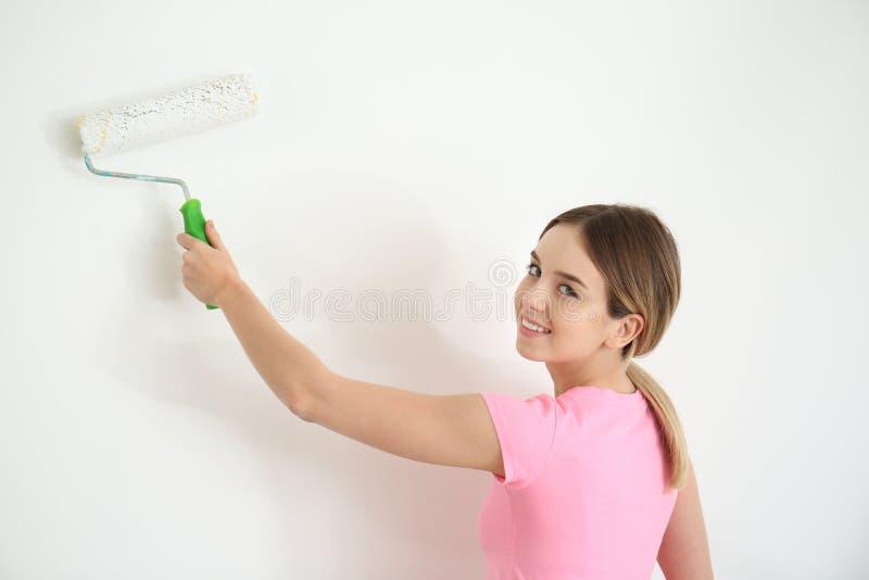 Pittore femminile che per mezzo del rullo per la ristrutturazione del colore della parete all'interno fotografia stock libera da diritti