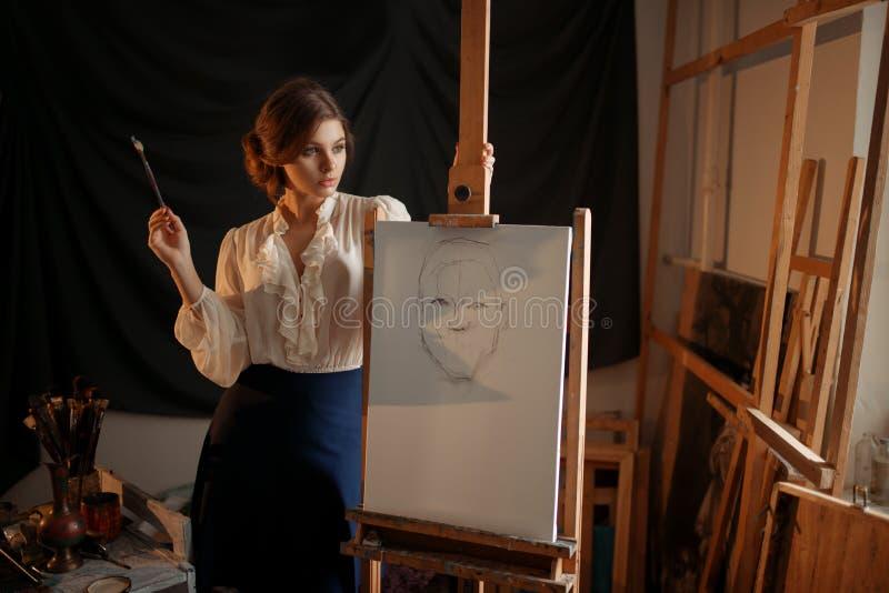 Pittore femminile con la condizione della spazzola contro il cavalletto fotografie stock libere da diritti