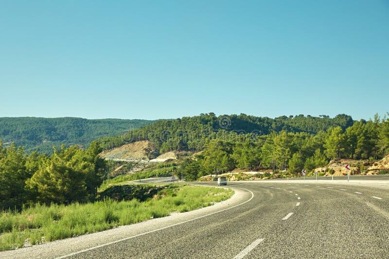 Pittoresk berghuvudväg med den tomma vägen för skogasfalt arkivbilder