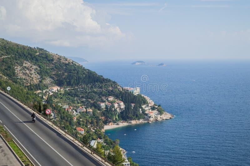 Pittoresk kust- väg med motorcykeln och sikt på Dubrovnik fotografering för bildbyråer