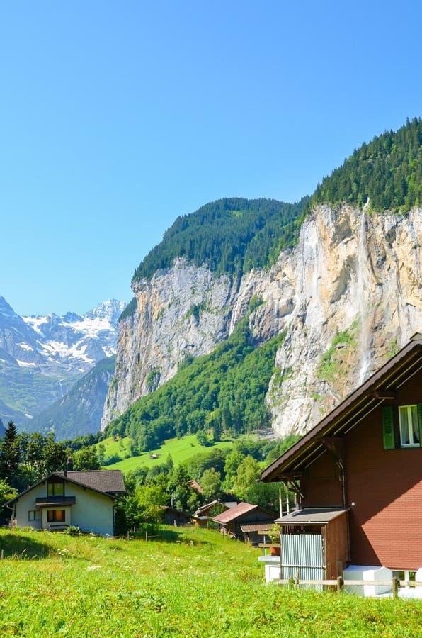 Pittoresk by Lauterbrunnen i Schweiz med berömda Staubbach nedgångar i bakgrund En av schweiziska viktiga turist- dragningar royaltyfria bilder