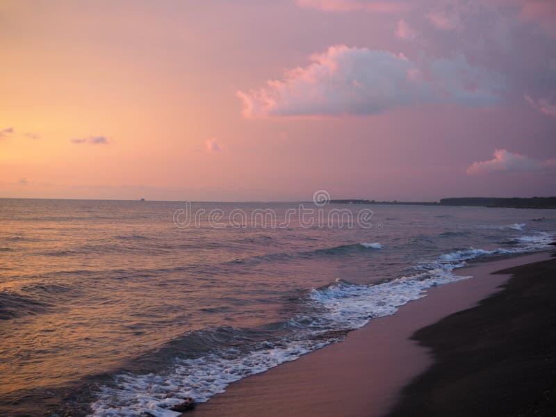 Pittoresk rosa solnedgång på färger för sand för sjöstrandhav härliga i himmelmolnen royaltyfri foto