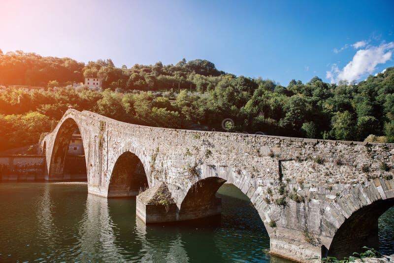 Pittoresk sikt av den medeltida Ponte för stenbågebro dellaen Maddalena över floden Serchio i Borgo en Mozzano, Lucca, Tuscany, arkivfoton
