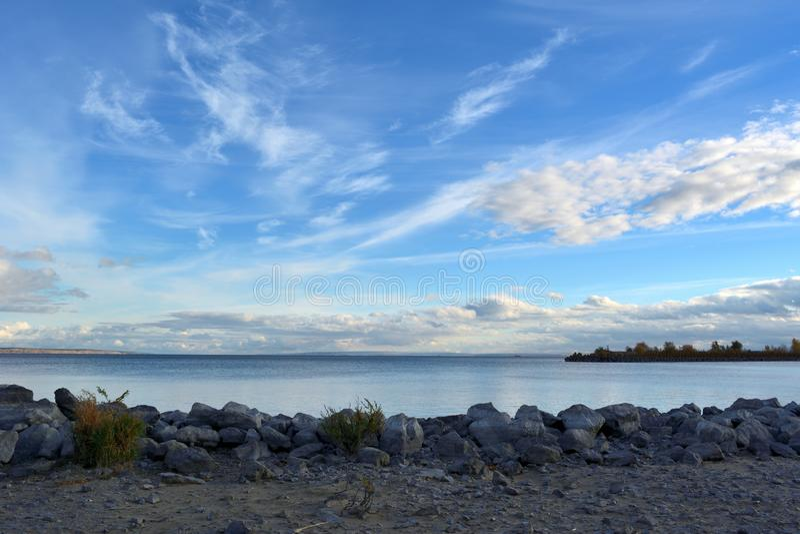 Pittoreskt landskap med den blåa floden och gråa stenar på banken Härlig himmelpanorama med moln arkivbilder