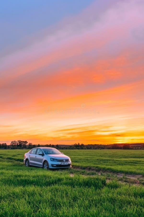 Pittoreskt landskap på solnedgången med en bil Volkswagen Polo Vento arkivbilder