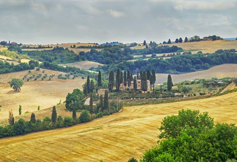 Pittoreskt Tuscany landskap med Rolling Hills, dalar, soliga fält, cypressträd längs spolning av den lantliga vägen, hus på en ku royaltyfri fotografi