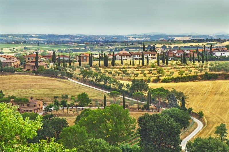 Pittoreskt Tuscany landskap med Rolling Hills, dalar, soliga fält, cypressträd längs spolning av den lantliga vägen, hus på en ku arkivfoton