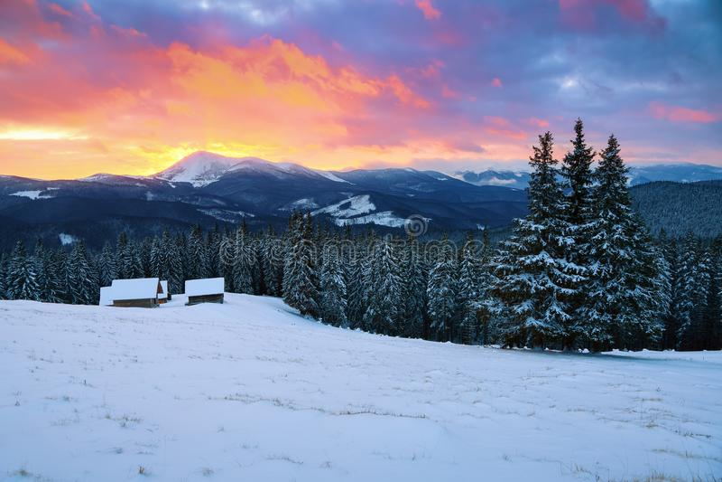 Pittoreskt vinterlandskap med kojor, snöig berg royaltyfri fotografi