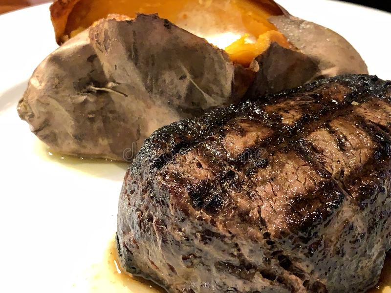 Fillet mignon with grill marks and sweet potato on a white plate. Pittsburgh style grilled beef for dinner with orange sweet potato with butter royalty free stock photography