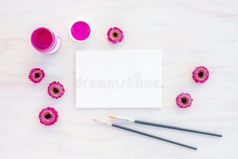 Pittura acrilica rosa luminosa e tela in bianco immagini stock