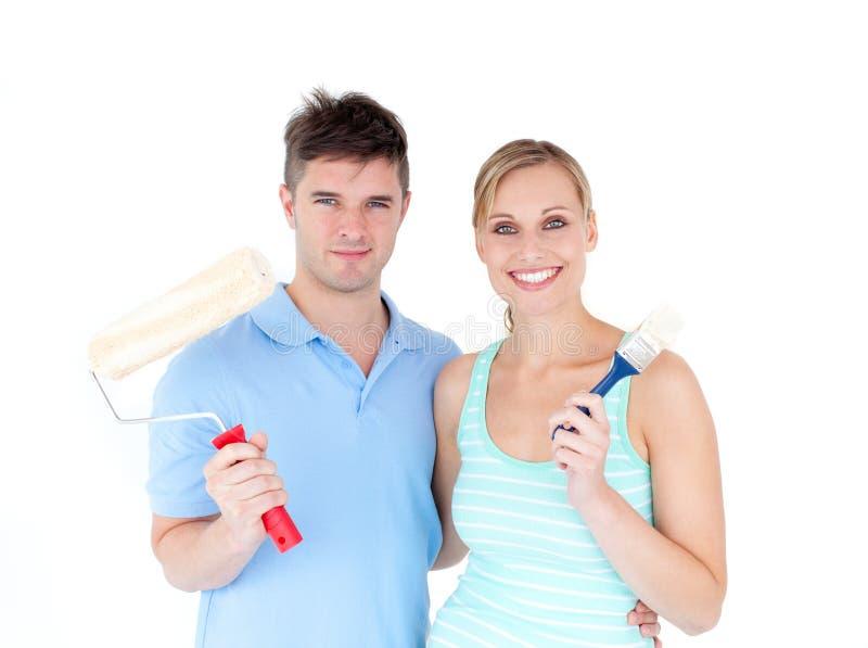 Pittura amorosa delle coppie nella loro nuova casa fotografia stock