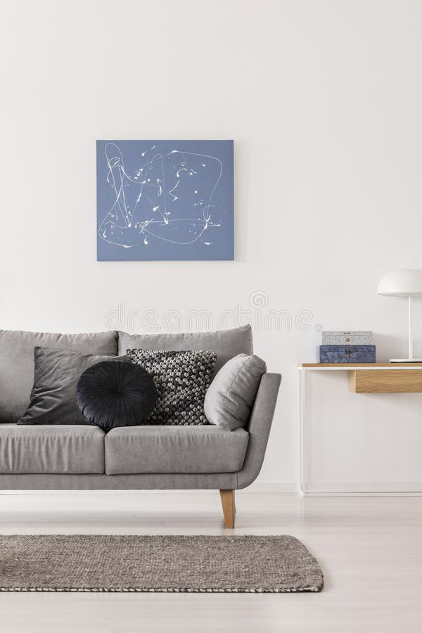 Pittura astratta blu sulla parete bianca del salone alla moda interna con la tavola grigia di console e dello strato fotografie stock