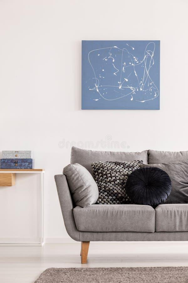 Pittura astratta blu sulla parete bianca del salone contemporaneo interna con il divano grigio con i cuscini immagini stock