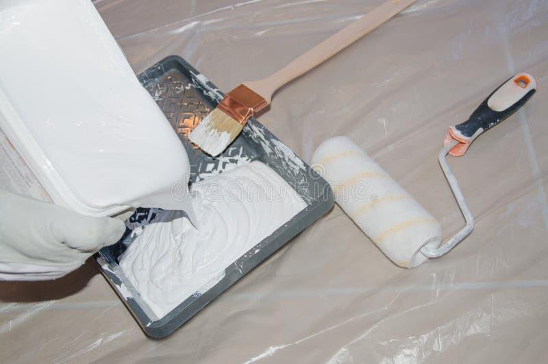 Pittura bianca di versamento del pittore immagini stock