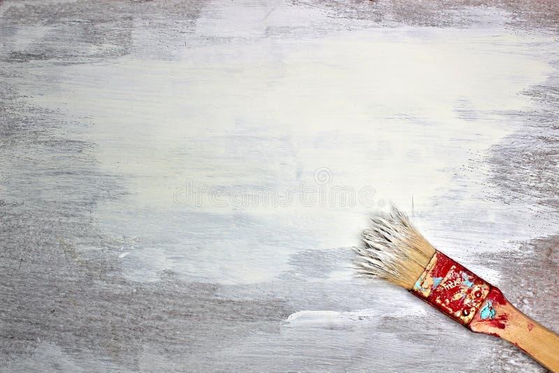 Pittura bianca fresca su fondo di legno Vecchio pennello con pittura e trovarsi sull'angolo più basso immagine stock libera da diritti