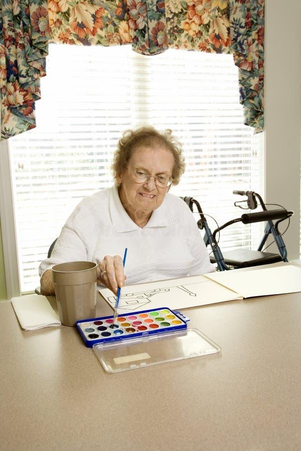 Pittura caucasica anziana della donna con gli acquerelli. immagine stock libera da diritti