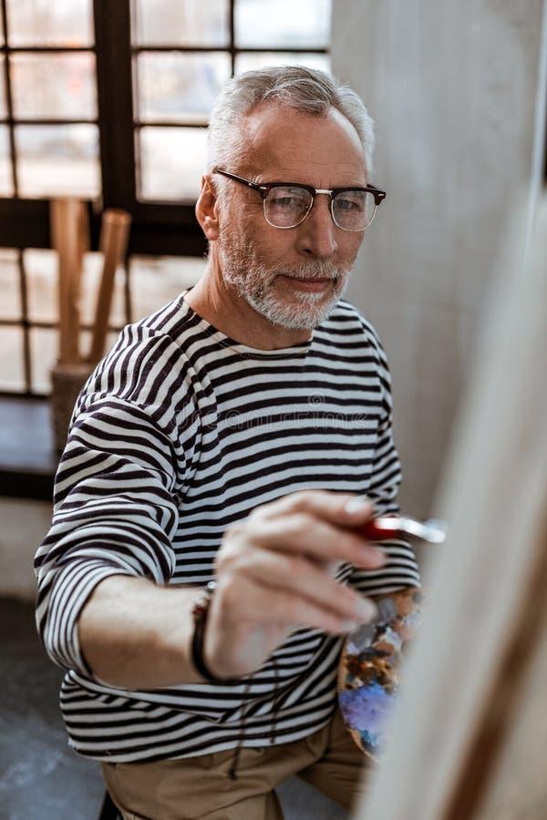 Pittura dagli occhi scuri dell'artista sulla tela mentre avendo ispirazione immagini stock libere da diritti