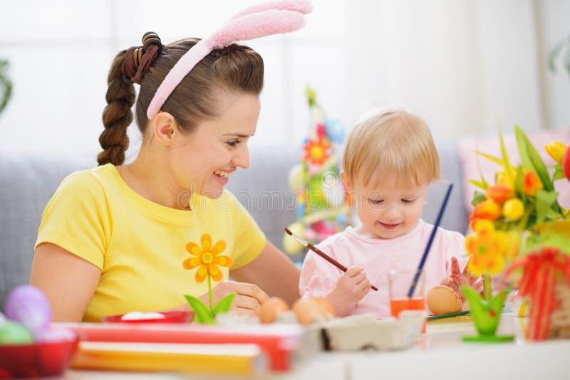 Pittura del bambino e della madre sulle uova di Pasqua immagine stock libera da diritti