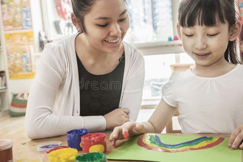 Pittura del dito dello studente e dell'insegnante nella classe di arte fotografie stock