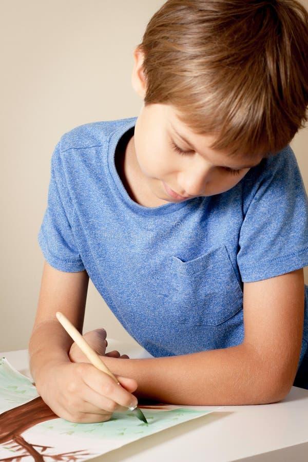 Pittura del ragazzo con il pennello e le pitture variopinte dell'acquerello e di gouache fotografia stock