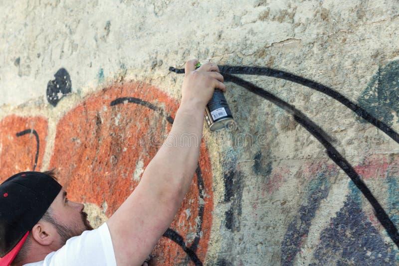 Pittura dell'artista dei graffiti con la bottiglia dello spruzzo di aerosol immagini stock